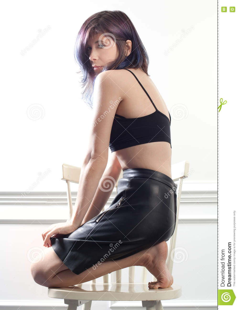 45b458309 An image of a pretty young woman in a black leather skirt kneeling barefoot  on a chair