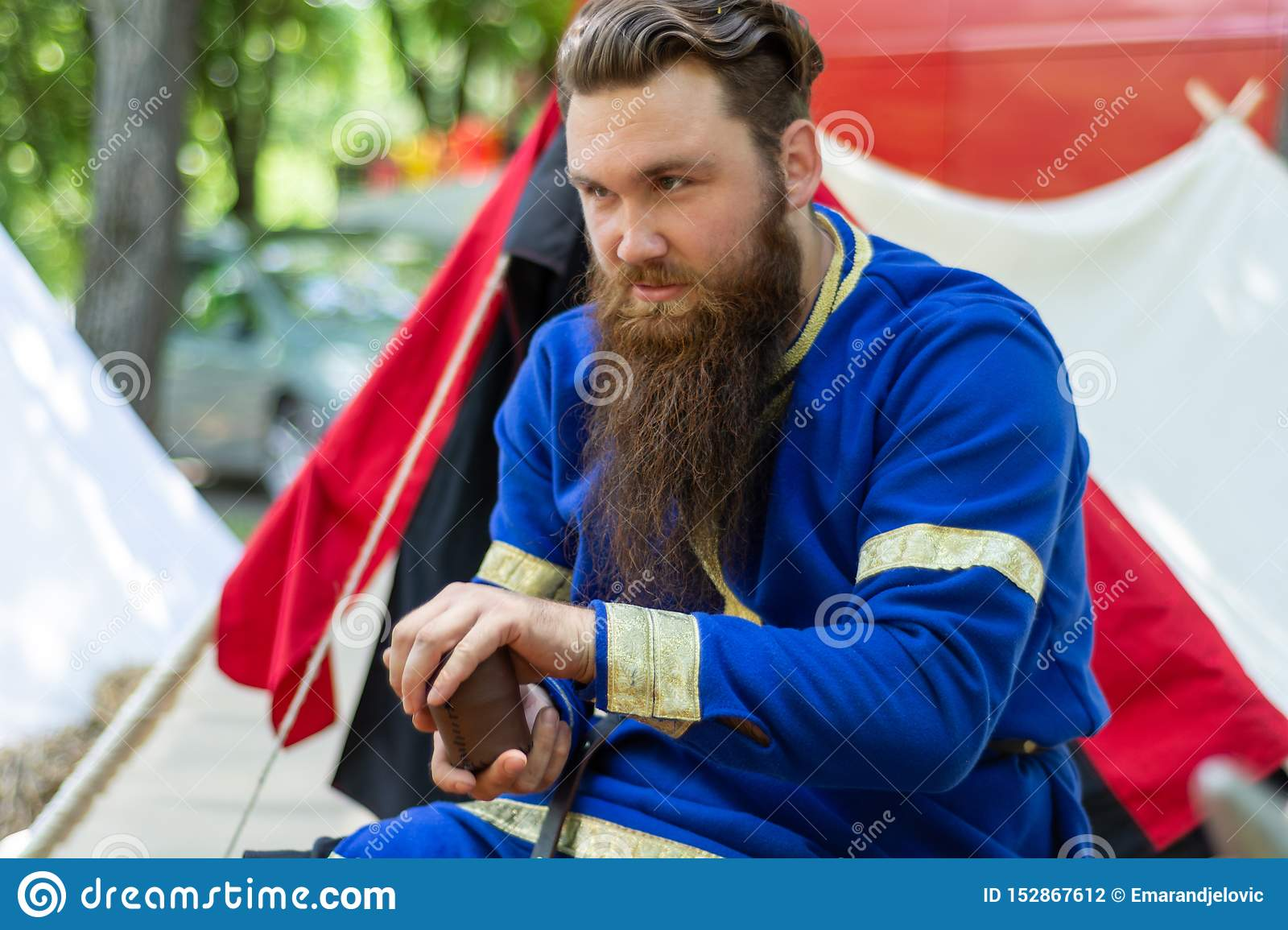 Knight with a beard in a blue traditional suit sits in front of the tent and plays an old dice game