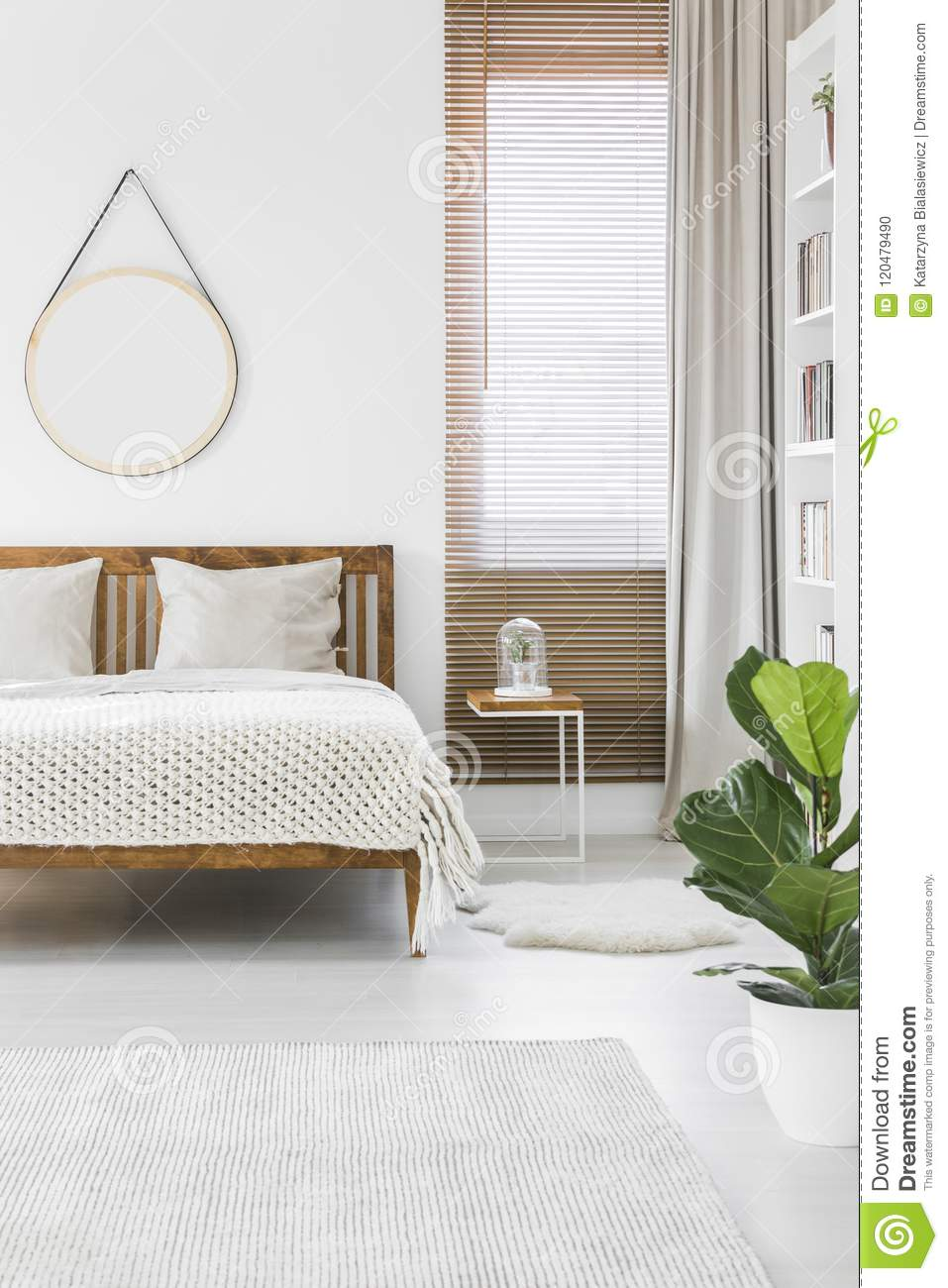 Knit blanket placed on wooden double bed in bright bedroom inter
