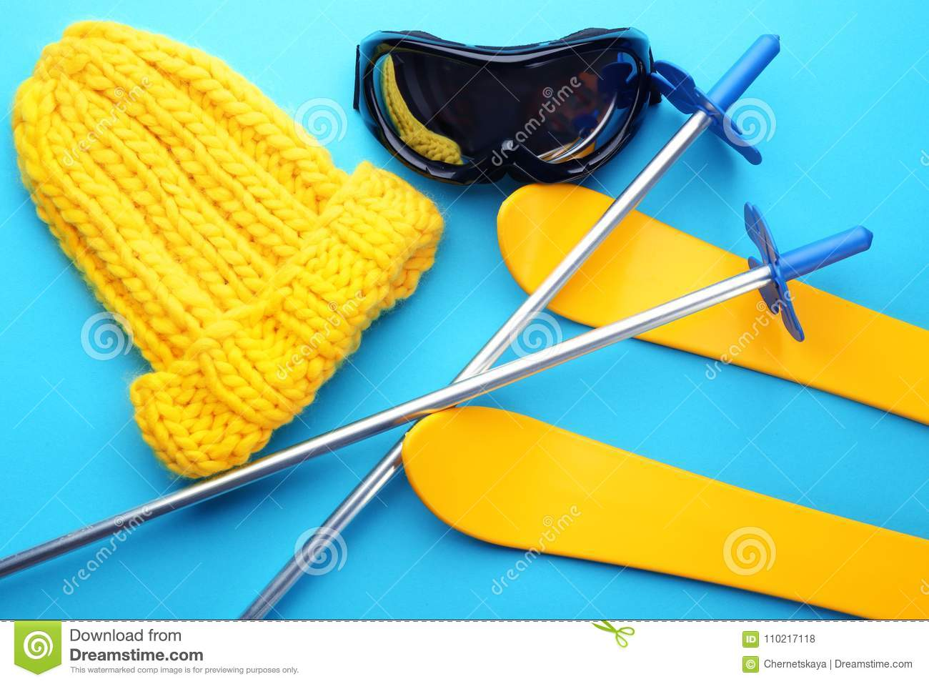 Knitted hat with ski outfit on color background.