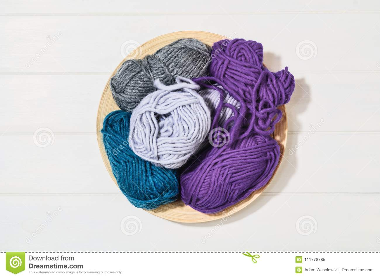 Knitting accessories top view on white wooden background