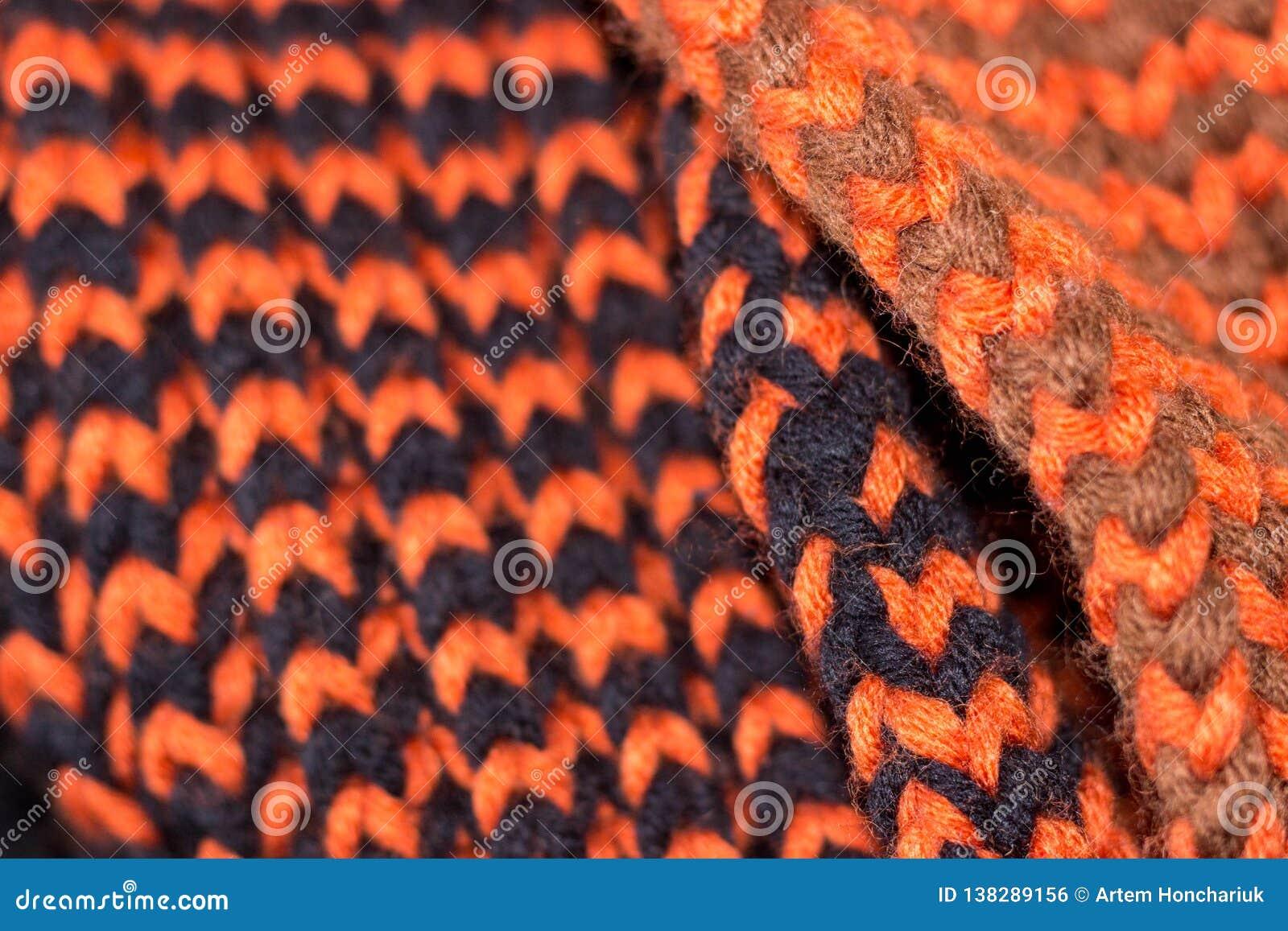 Knitting Achtergrond gebreide textuur Heldere breinaalden Oranje en zwart wolgaren voor het breien