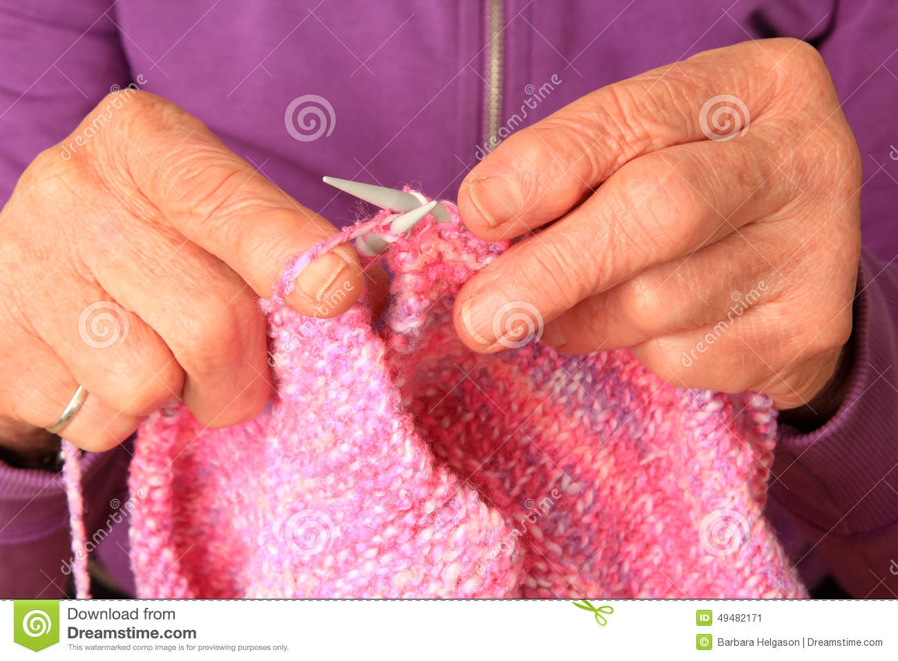 Knitting With Arthritic Hands : Hands knitting a magenta scarf stock photography