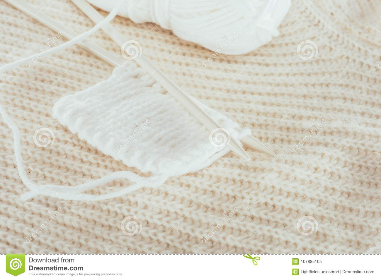 Knitting needles with white woolen yarn