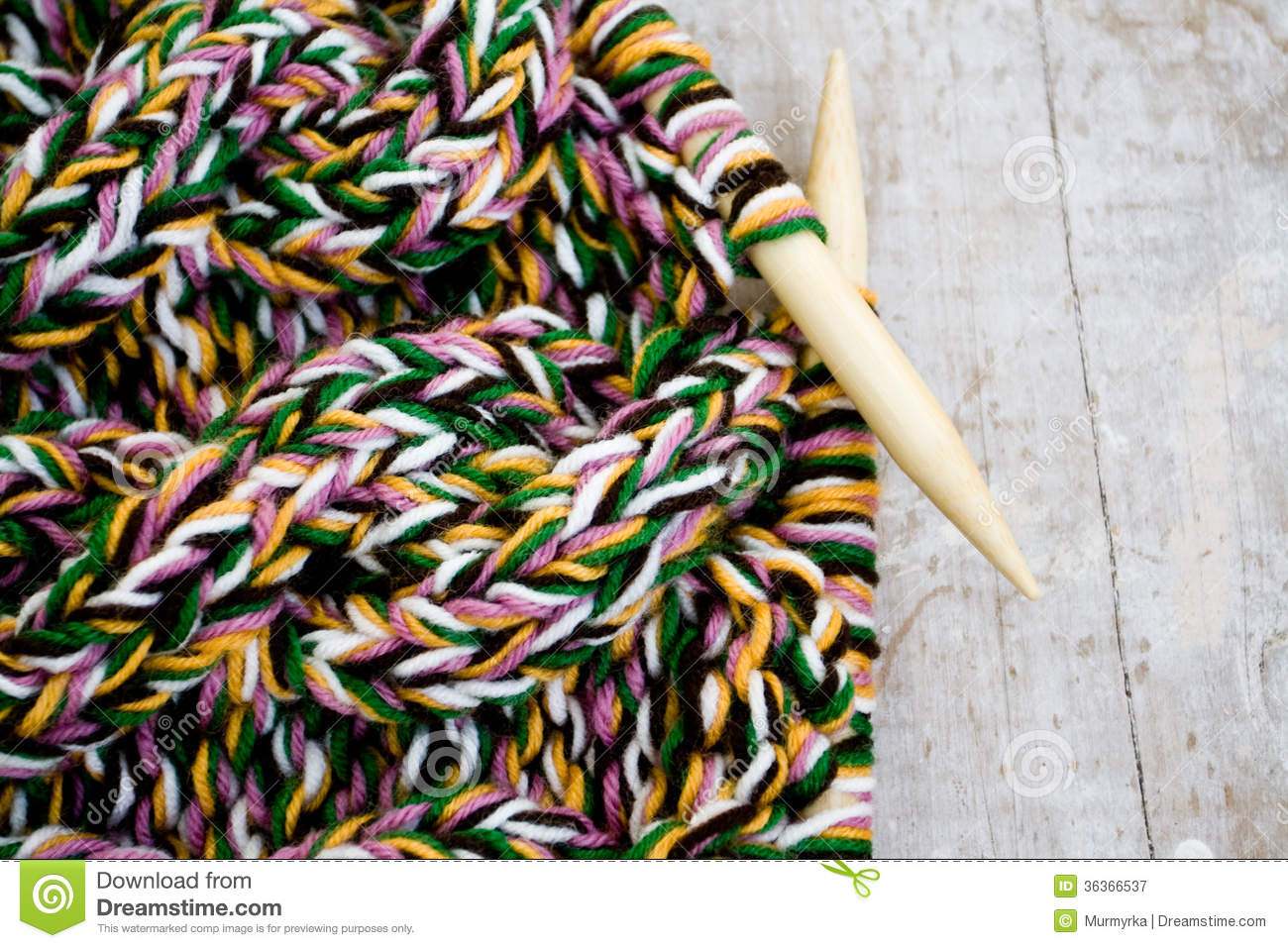 knitting needles and yarn on wooden background royalty