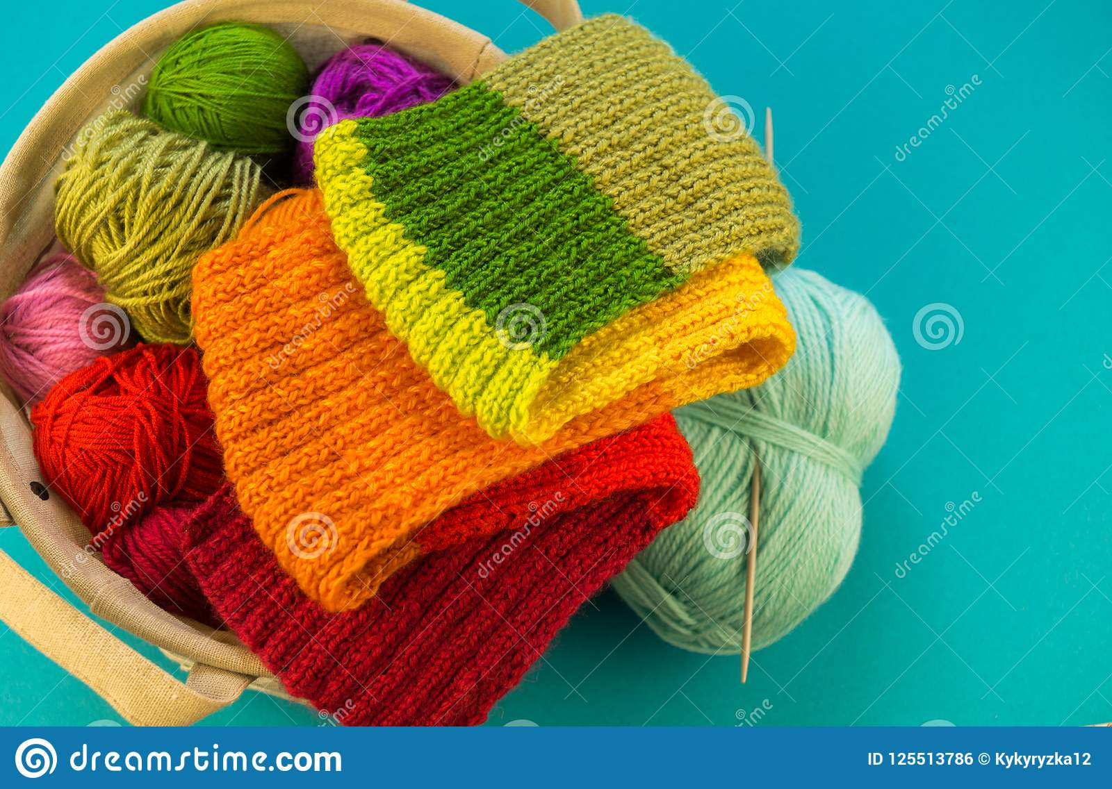 Knitting a rainbow scarf and hat Blue background