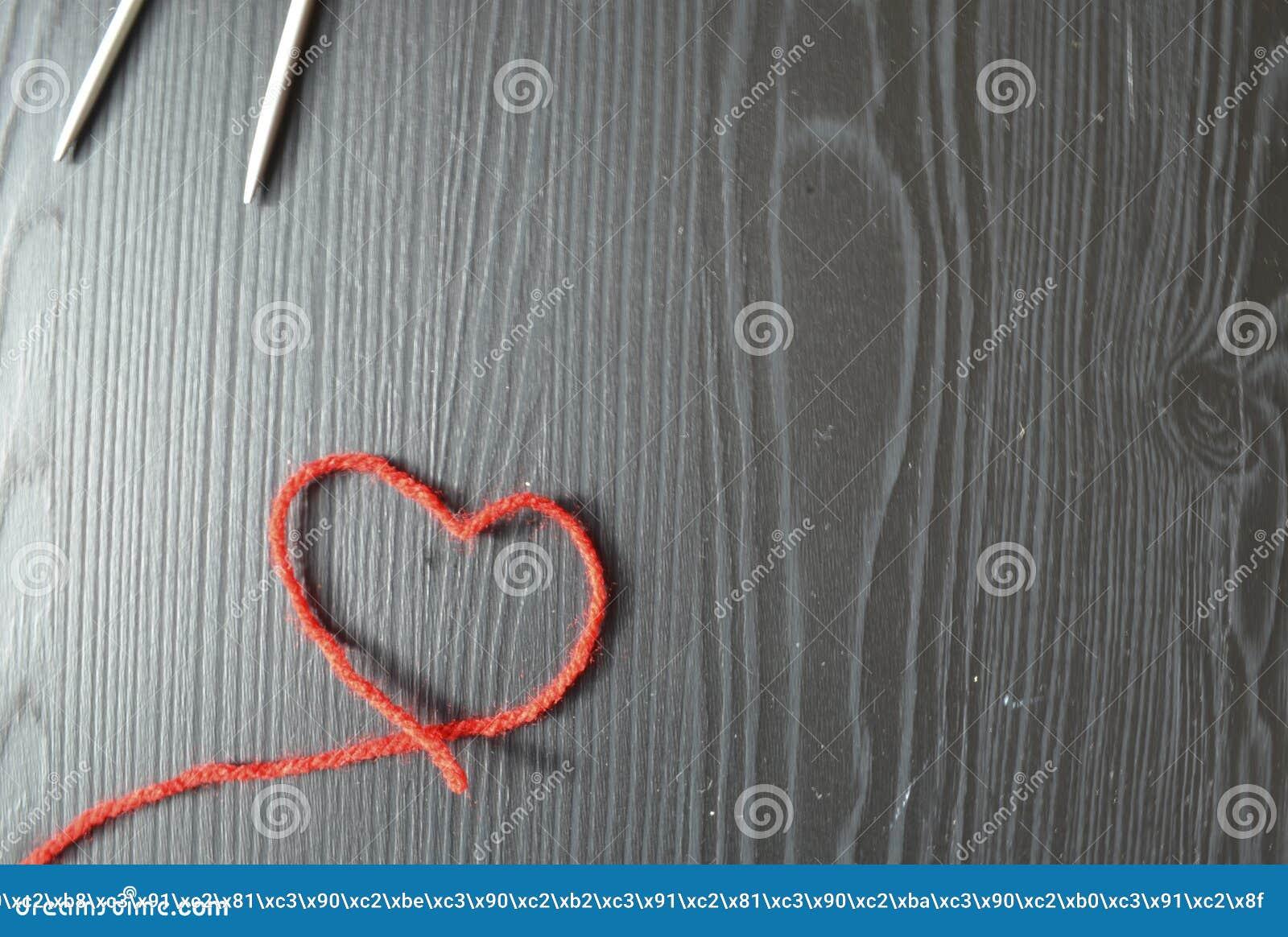 Knitting Rode draad op houten achtergrond Breinaalden
