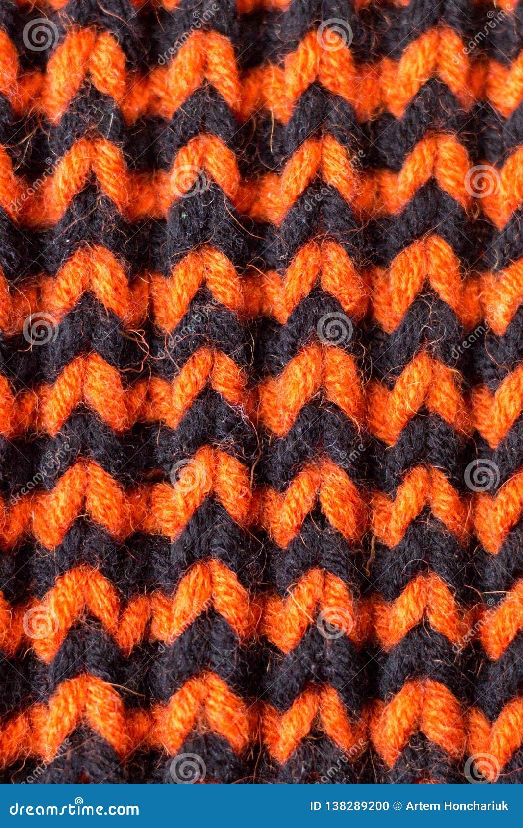 Knitting Textura hecha punto fondo Agujas que hacen punto brillantes Hilado de la naranja y de lana negra para hacer punto