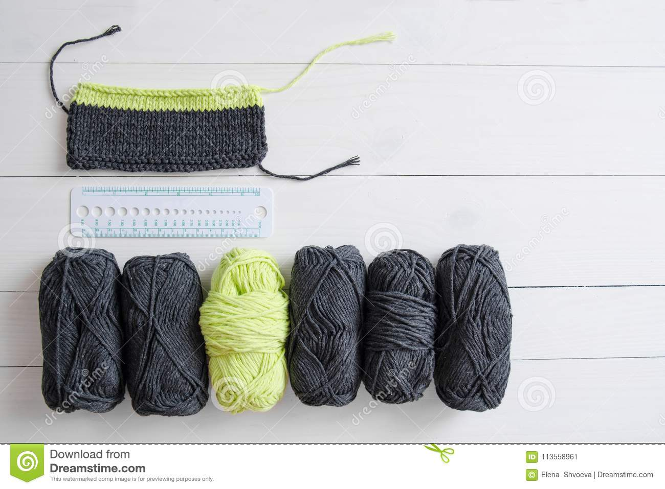 Knitting yarn with knitting pattern and ruler on white wooden background. The concept of Hobbies, crafts, the beginning of a new k