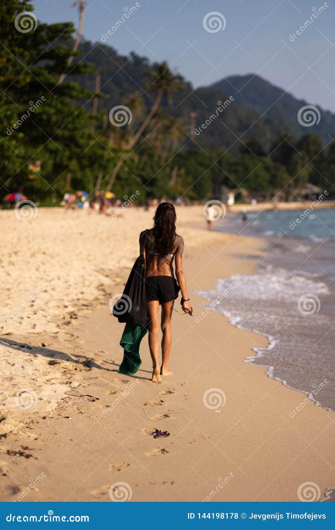 KNOCK-OUT CHANG, THAILAND - APRIL 9, 2018: Äkta asiat dem flicka som promenerar havet på en strand med att förbluffa sikt -