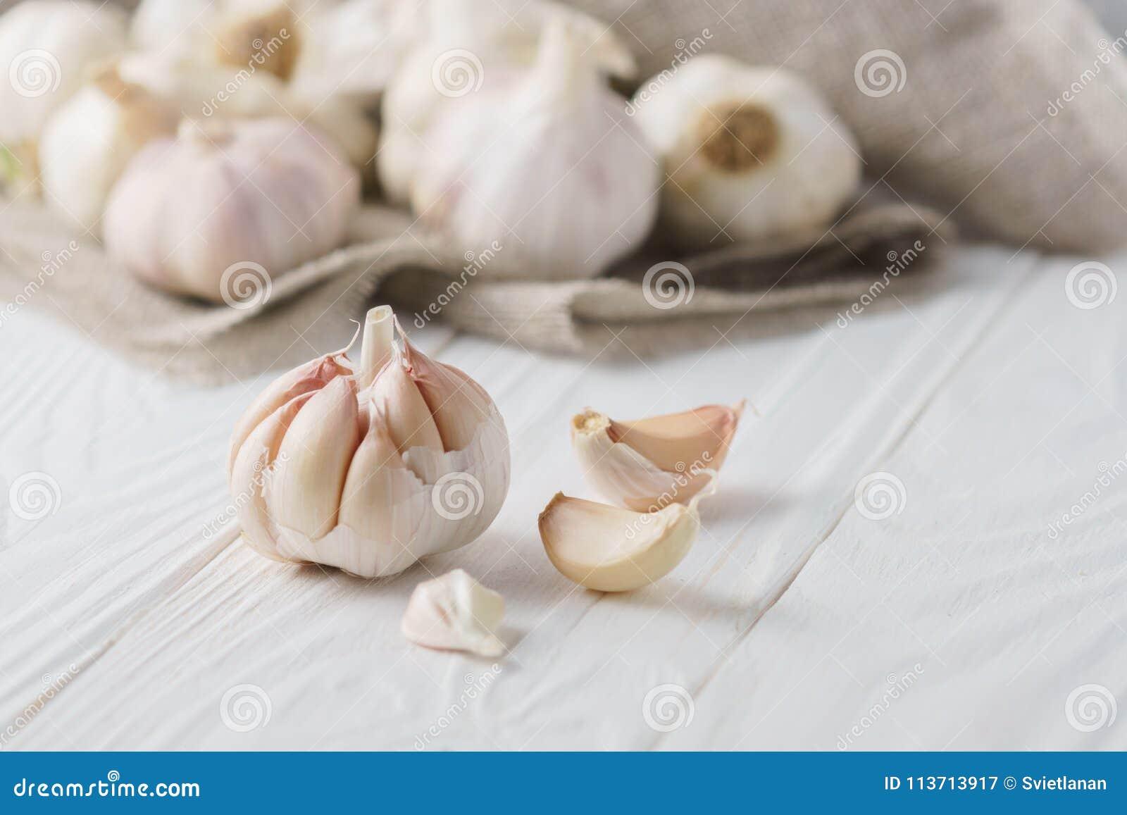 Knoflookbollen met knoflookkruidnagels met canvas op wit hout