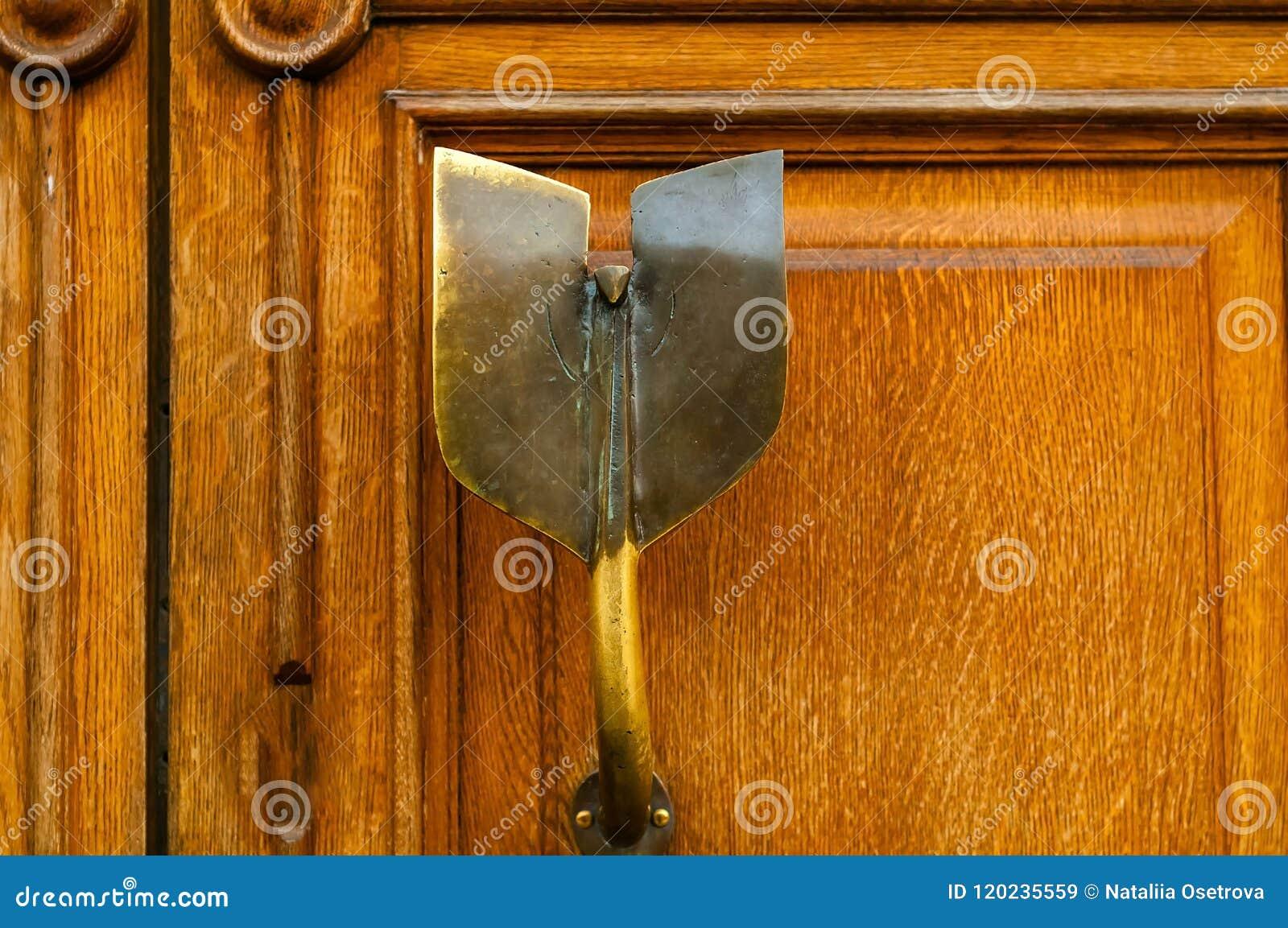 Knoppen för tappningjärndörren med prydnaden på träbakgrund, begrepp av antikviteten anmärker, naturligt ljus, kopieringsutrymme,