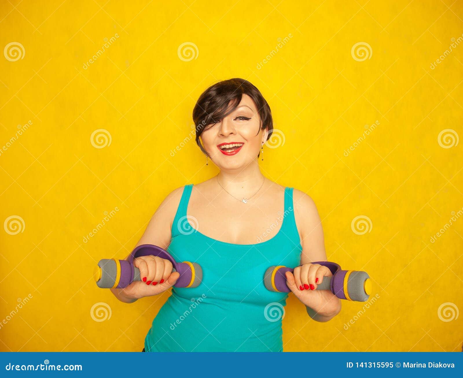Knubbig glad emotionell flicka med kort hår i en blå t-skjorta som gör sportar med hantlar för att vara sunt och förlora vikt på