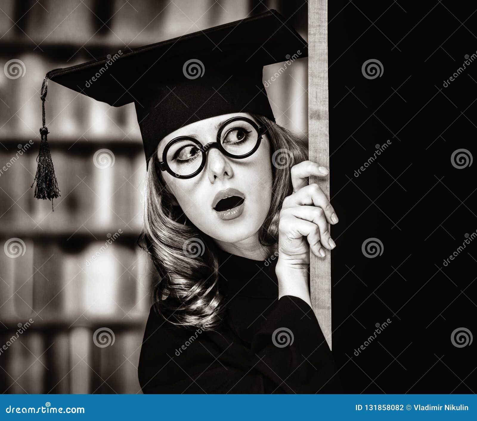 Kończyć studia studenckiej dziewczyny w akademickiej todze blisko blackboard