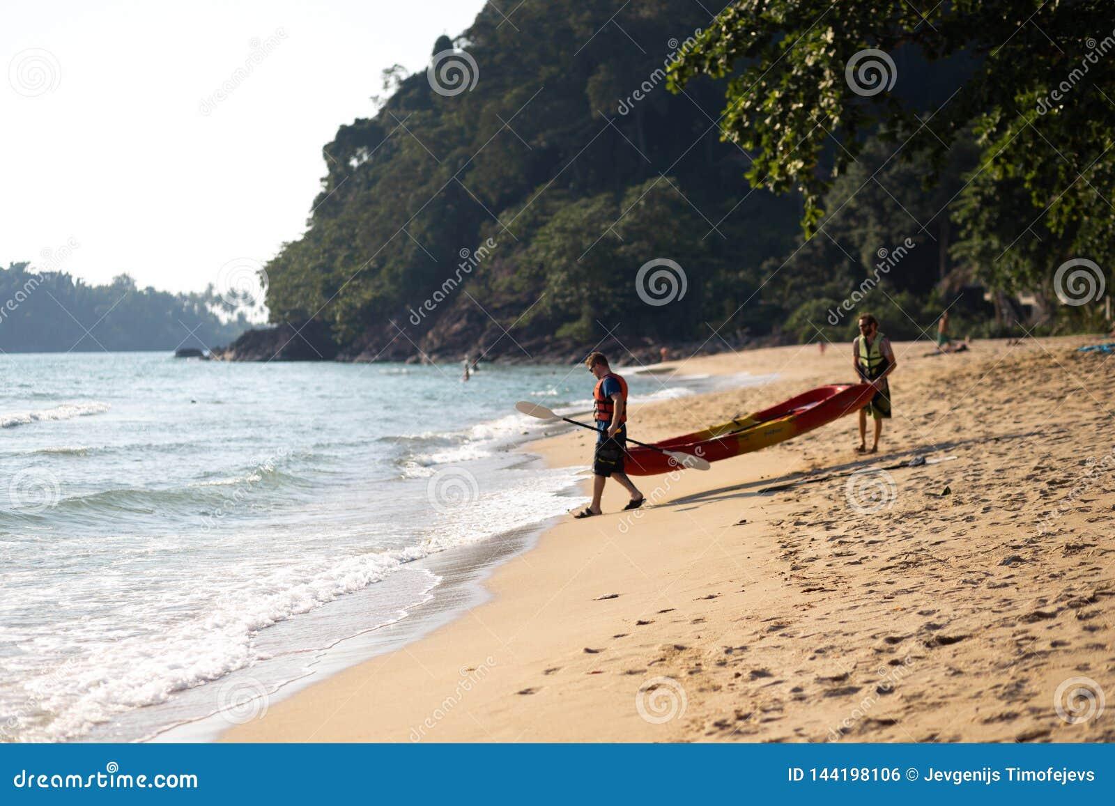 KO CHANG, THAILAND - APRIL 9, 2018: People men sweaming on a kayak boat - Beautiful tropical paradise beach