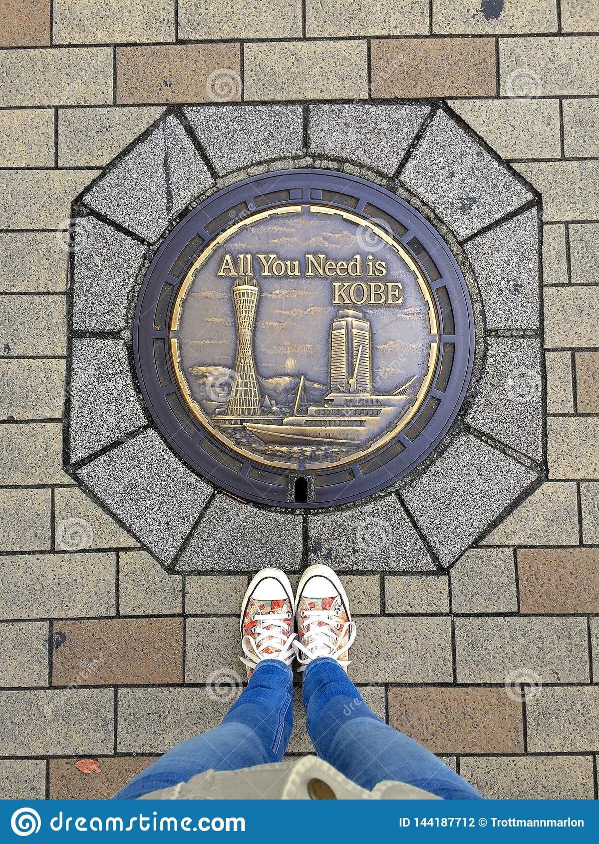 Female feet wearing sneakers standing in front of typical decorated Manhole of Kobe City, Japan