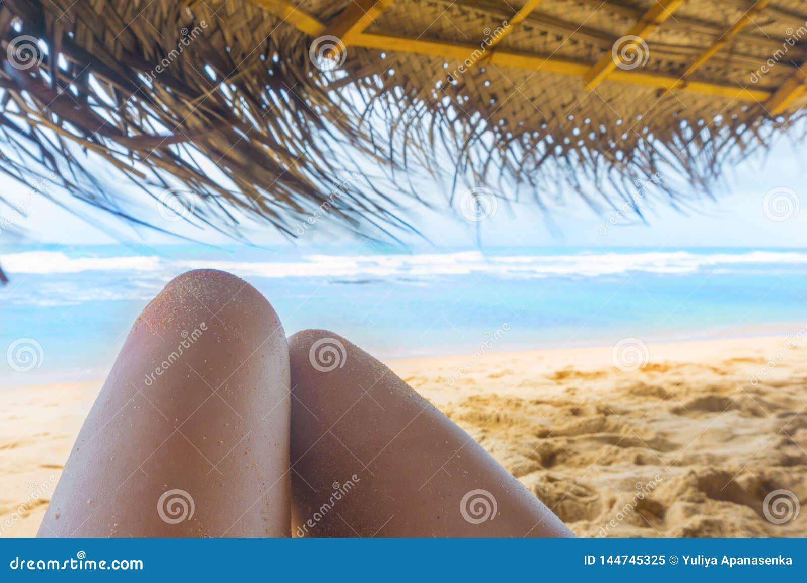 Kobiet nogi pod sunshade na pogodnej tropikalnej pla?y