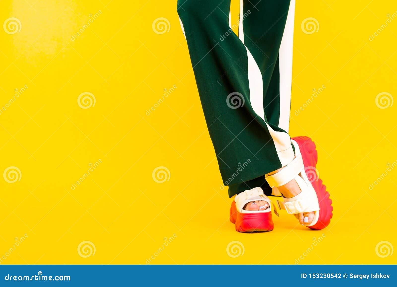 Kobiet nogi w sportów sandałach z czerwonymi podeszwami i zieleni spodniami z lampasami