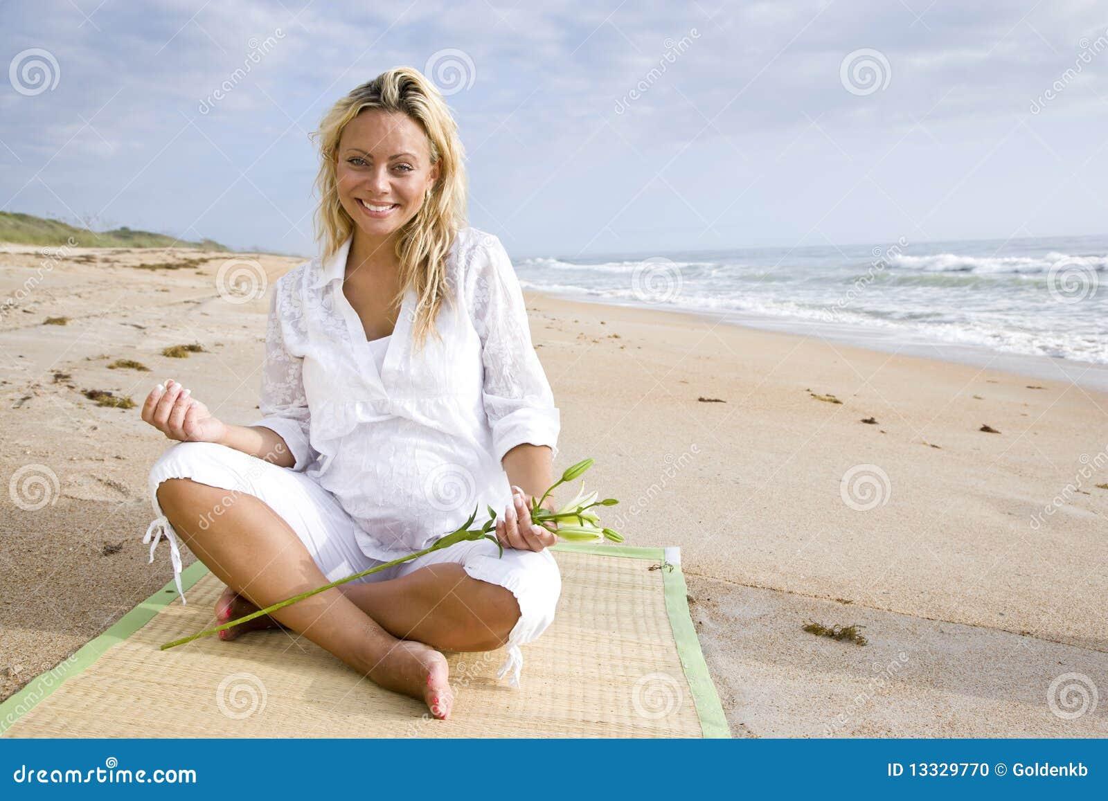 Kobiet plażowi ciężarni siedzący potomstwa