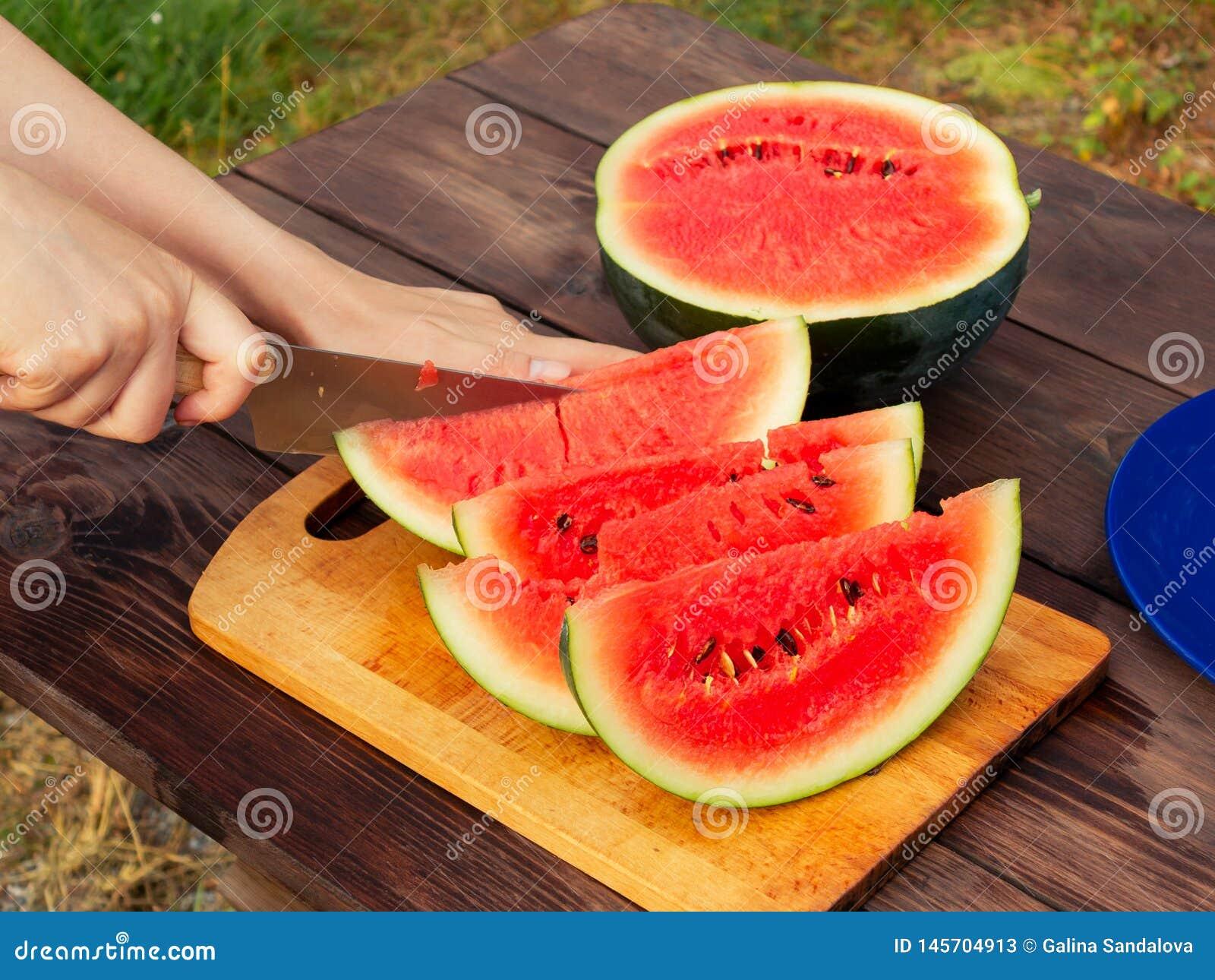 Kobiet ręki cią z nożem w plasterki dojrzały arbuz na drewnianym stole