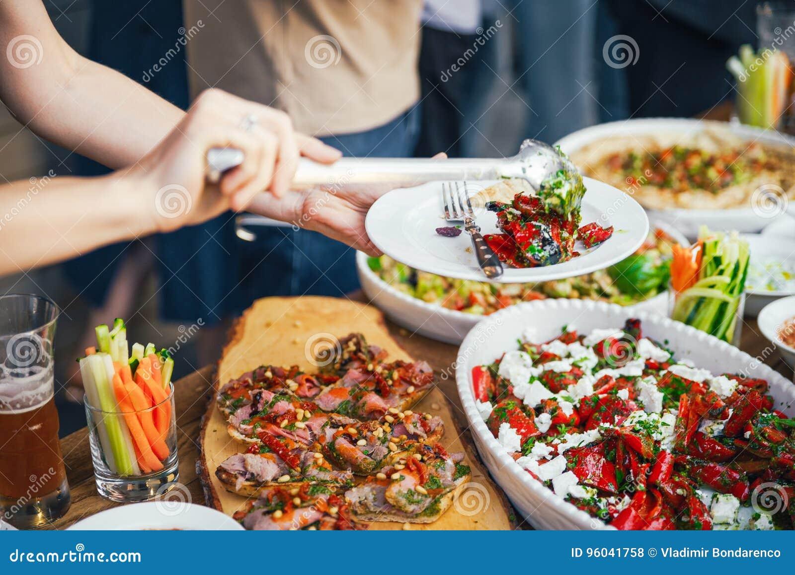 Kobiet ręki one wypiętrzają posiłek w talerzu lunch Pojęcie odżywianie bufet Jedzenie dinner Pojęcie udzielenie