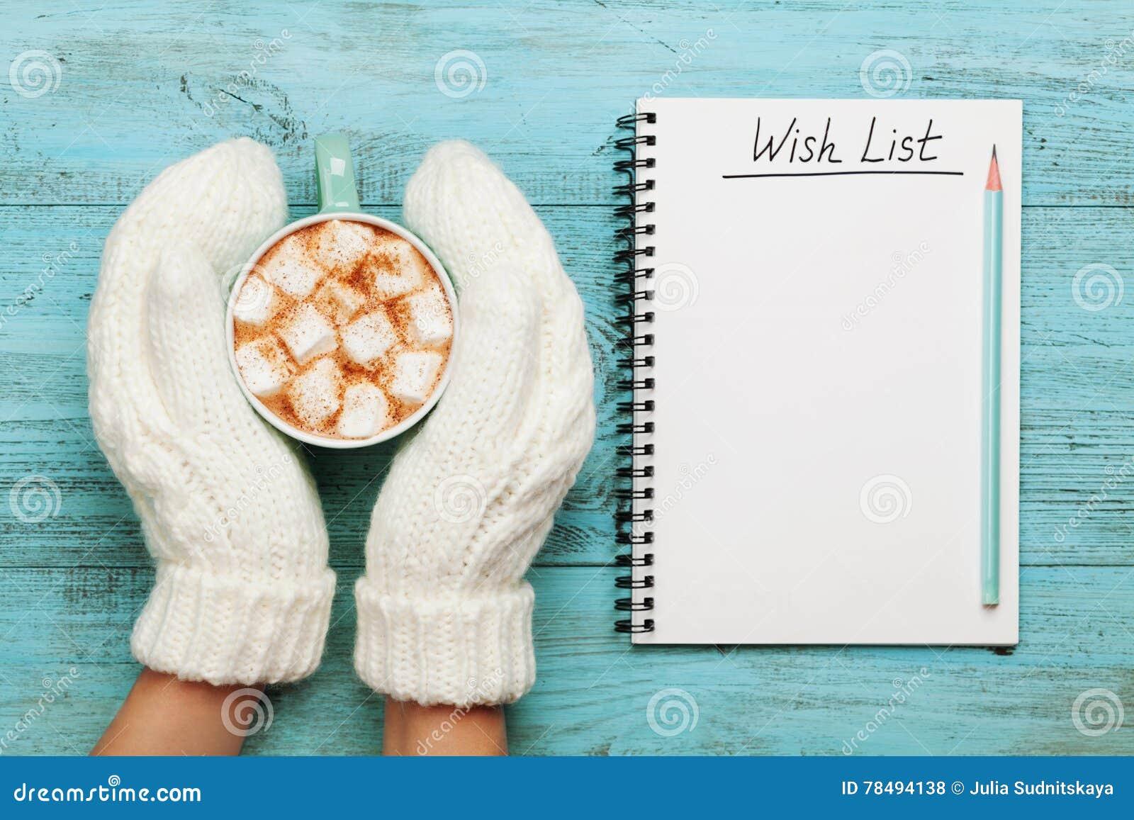 Kobiet ręki w mitynkach trzymają filiżankę gorący kakao lub czekolada z marshmallow i notatnikiem z listą życzeń na turkusowym ro