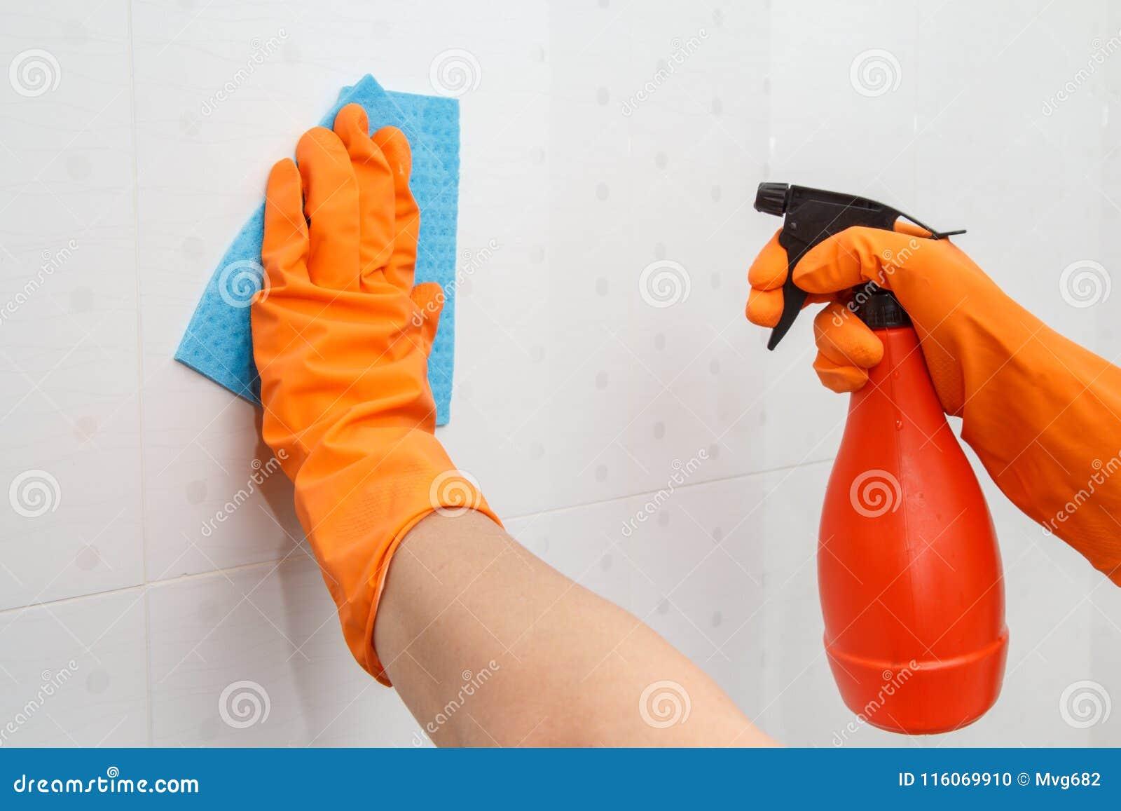 Kobiet ręki w pomarańczowej gumowej rękawiczka chwytów butelce detergent a
