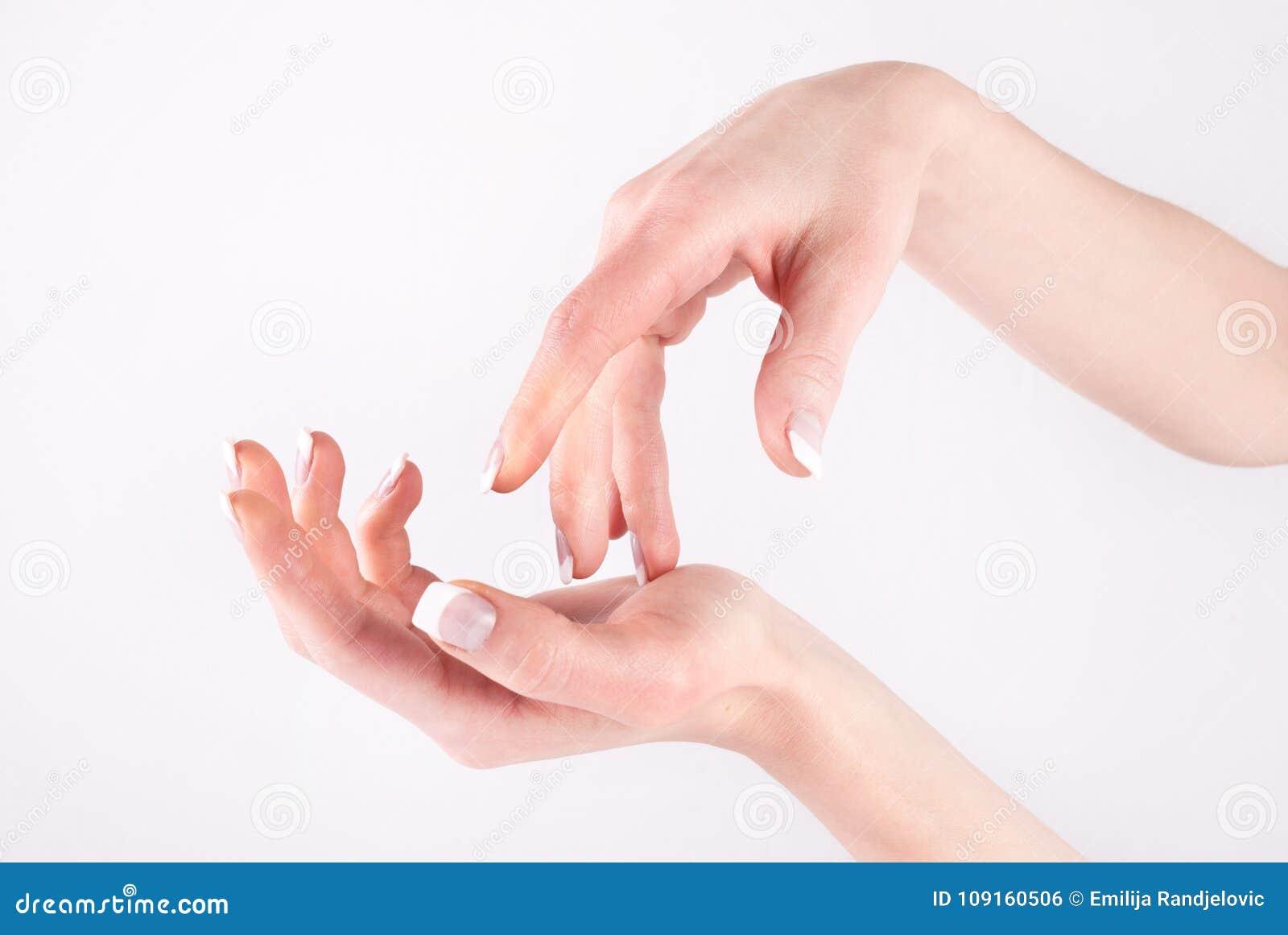 Kobiet ręki z fachowym francuskim gwoździa manicure em odizolowywającym na bielu