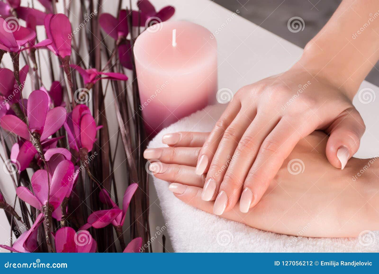 Kobiet ręki z Ombre francuza purpurami i gwoździami kwitną z aromatyczną świeczką w zdroju