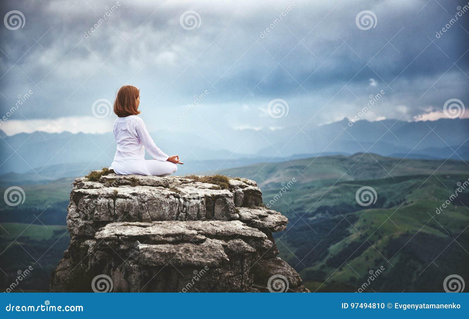 Kobieta ćwiczy joga i medytuje w lotosowej pozyci na mounta