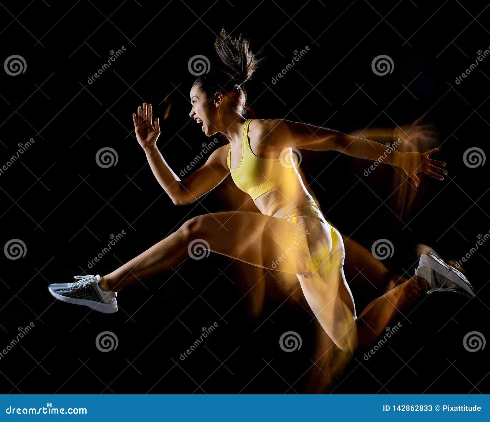 Kobieta ćwiczy sprawność fizyczną ćwiczy odosobnionego czarnego tła lightpainting skutek