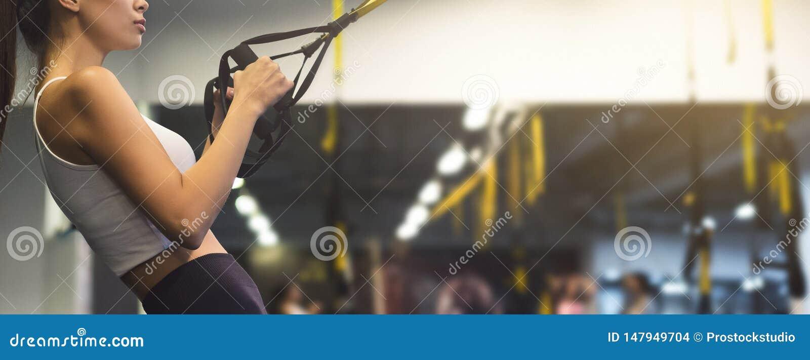 Kobieta ćwiczy z zawieszenie trenerem w gym, kopii przestrzeń