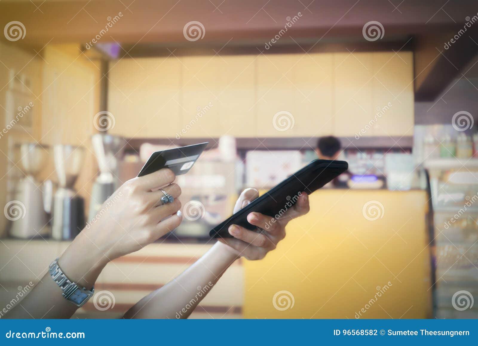 Kobieta azjata używa mądrze telefon i kredytową kartę robi zakupy online,