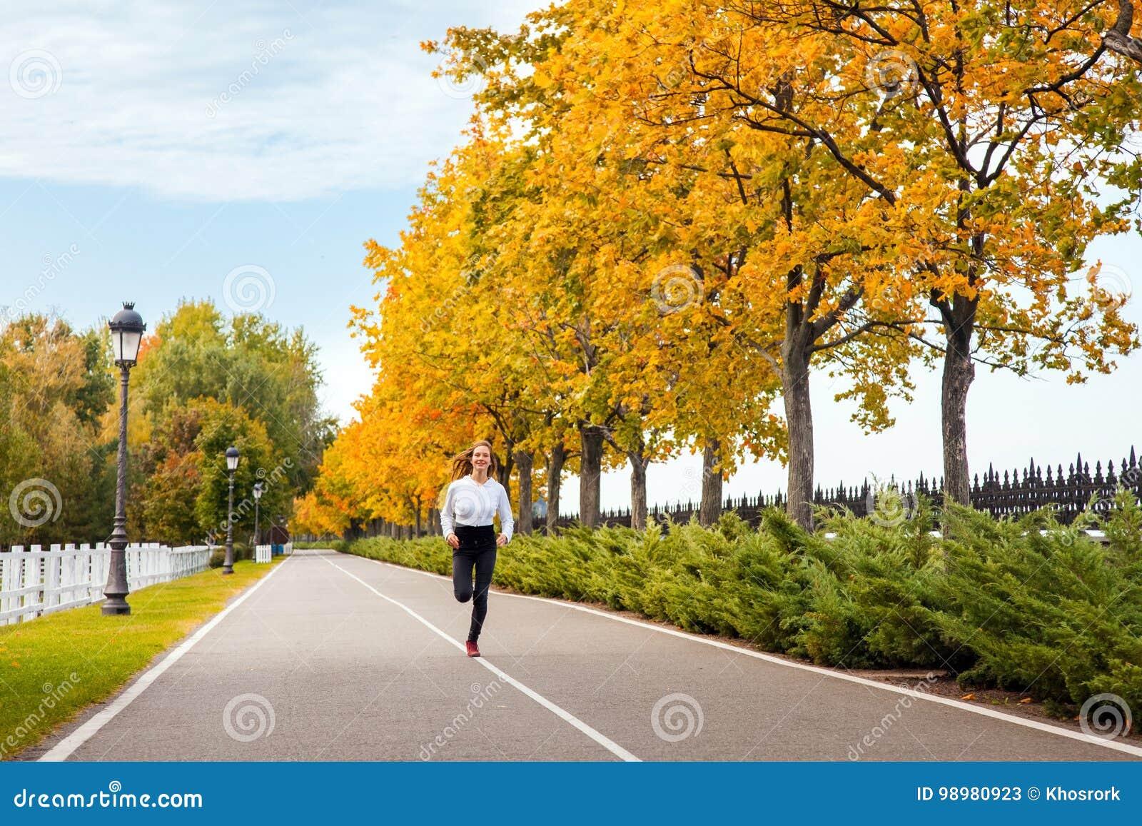 Kobieta bieg w jesieni lasowej Młodej dorosłej dziewczynie jogging w spadku