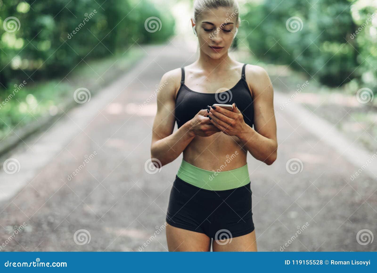 Kobieta biegacz Słucha muzyka na Smartphone w lato ranku parku Używać Bluetooth słuchawki Żeńska sprawności fizycznej dziewczyna