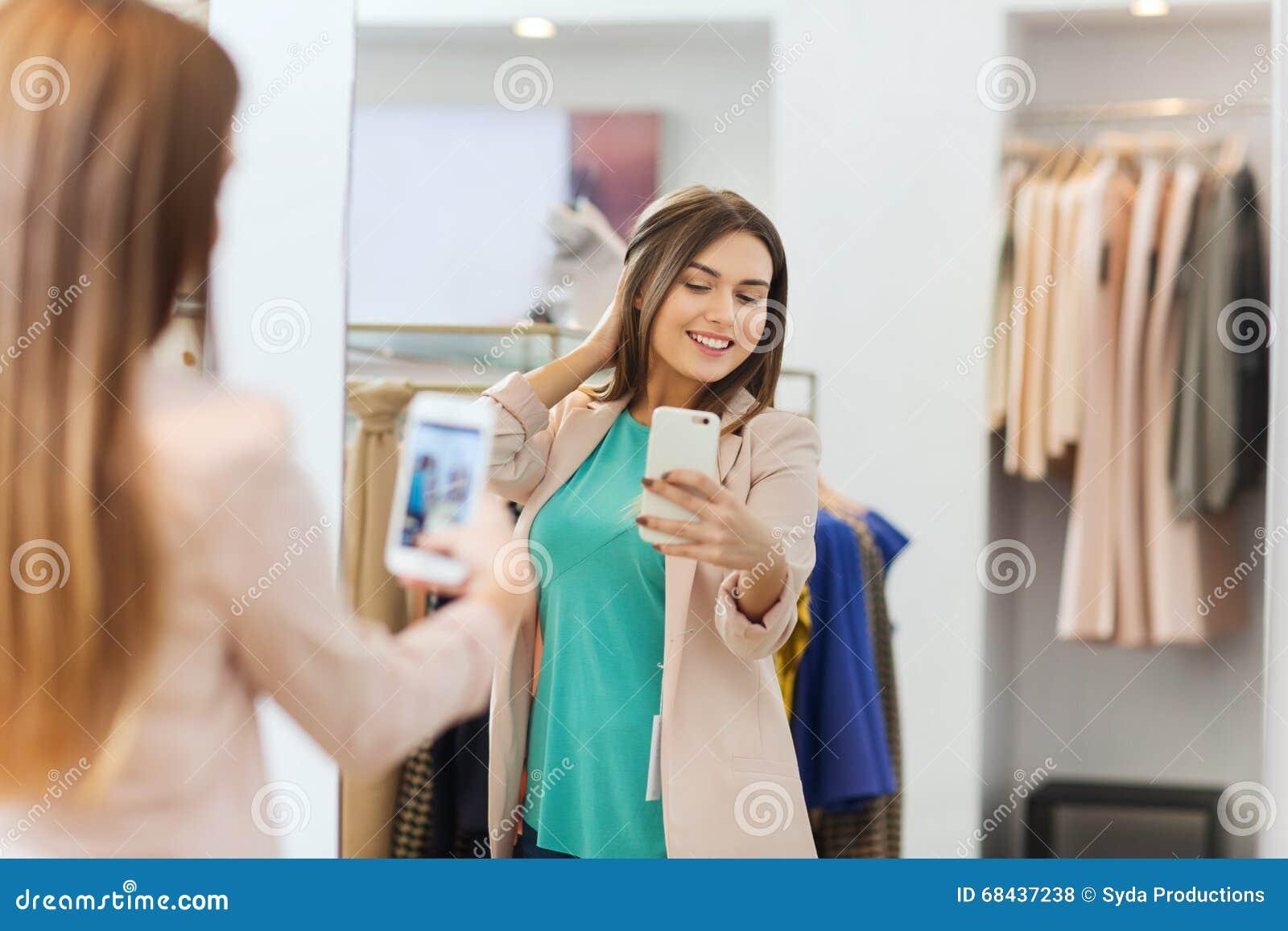 Kobieta bierze lustrzanego selfie smartphone przy sklepem