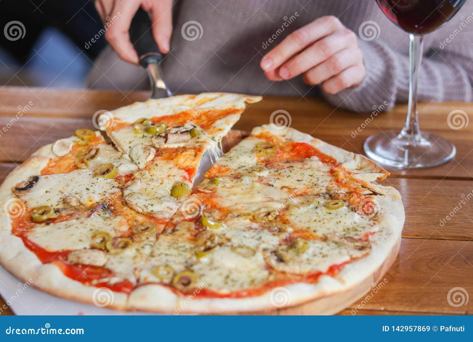 Kobieta bierze plasterek pokrojona pizza z mozzarella serem, pomidorami, pieprzem, oliwką, pikantność i Świeżym basilem, pizza wł