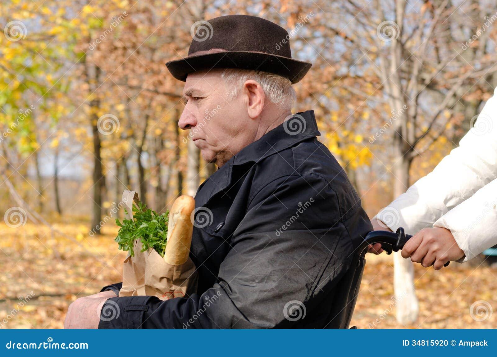 Kobieta bierze starsza osoba obezwładniającego mężczyzna zakupy