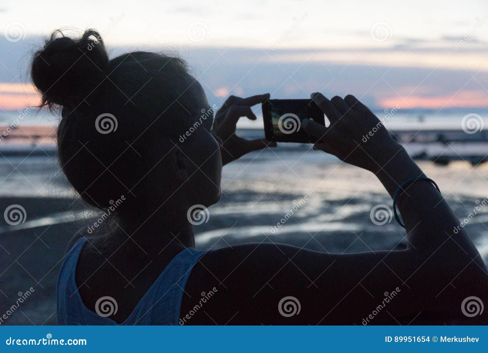 Kobieta bierze zmierzch nad morze na telefon kamerze