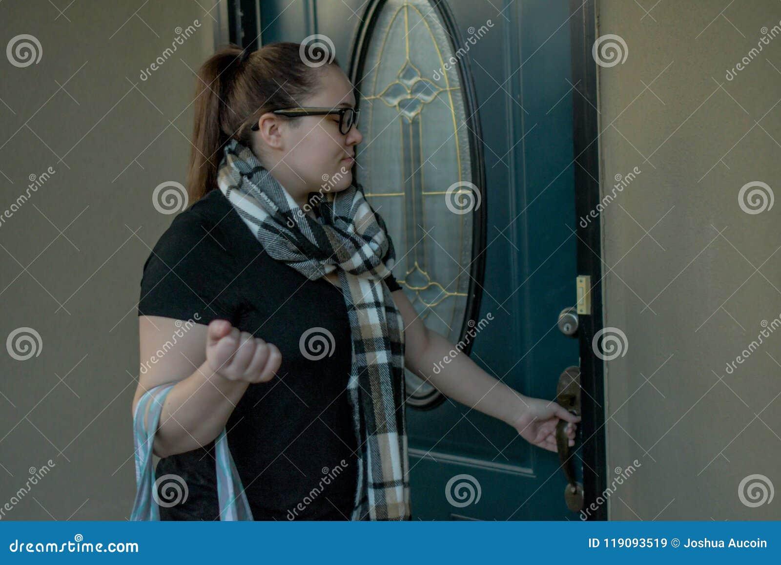 Kobieta blokuje jej dzwi wejściowy gdy opuszcza do domu z molton torbą nad jeden ręką