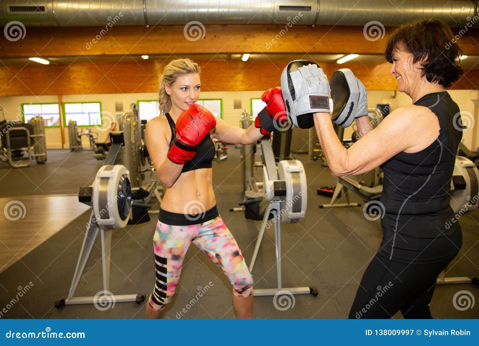 Kobieta bokser uderza rękawiczkę jego sparingowego partnera trenera osobistych kobiet starszy trening w gym