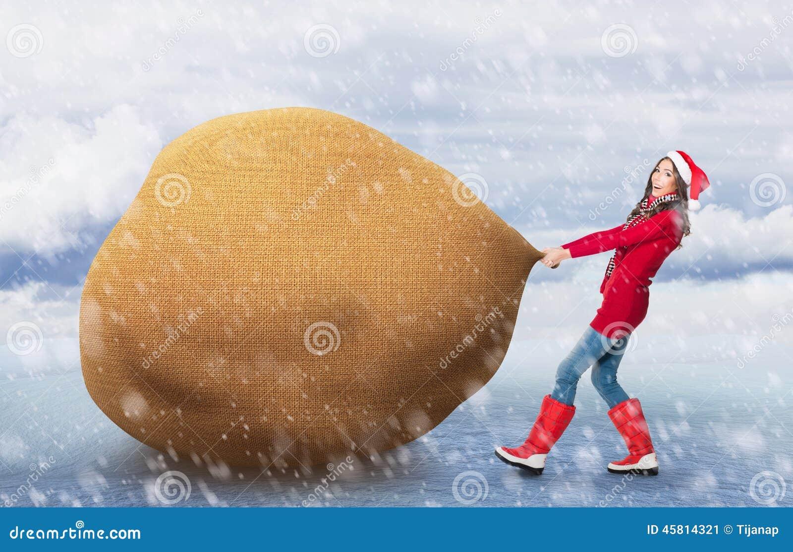Kobieta ciągnie dużego Santa torbę
