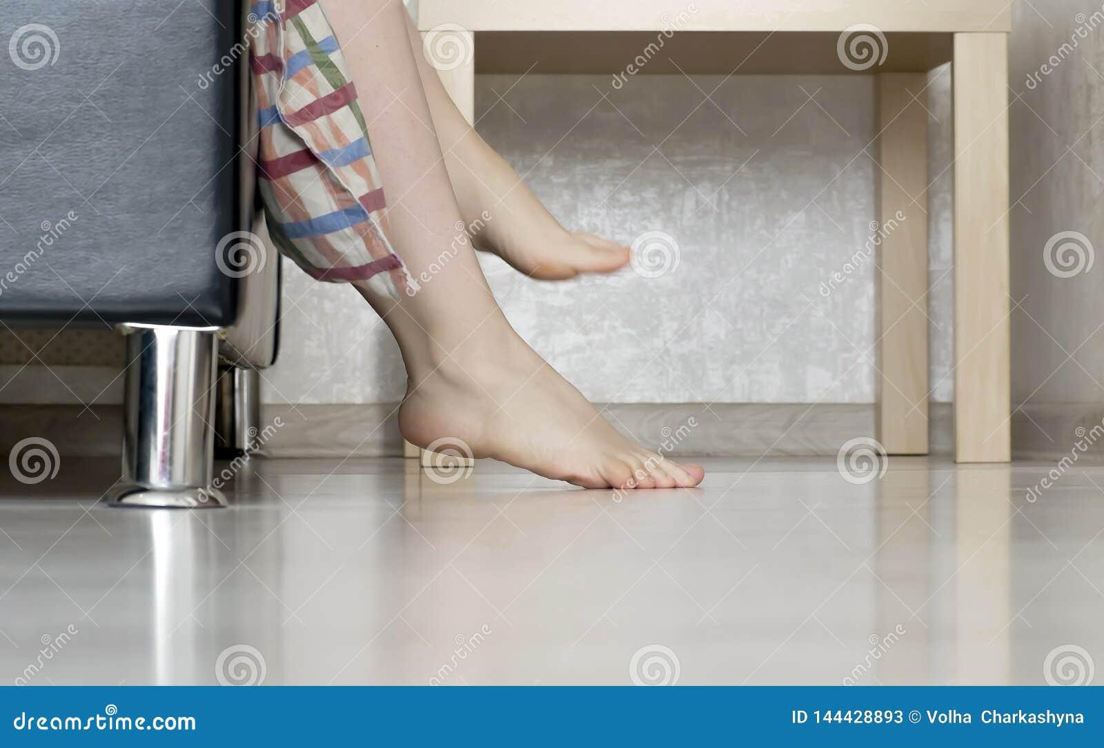 Kobieta ciągnie ona z łóżka nogi