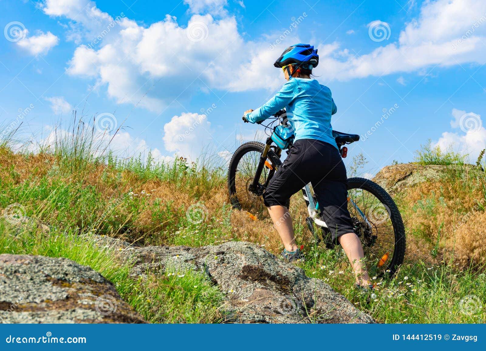 Kobieta cyklista pcha jej rower w górę stromego skłonu