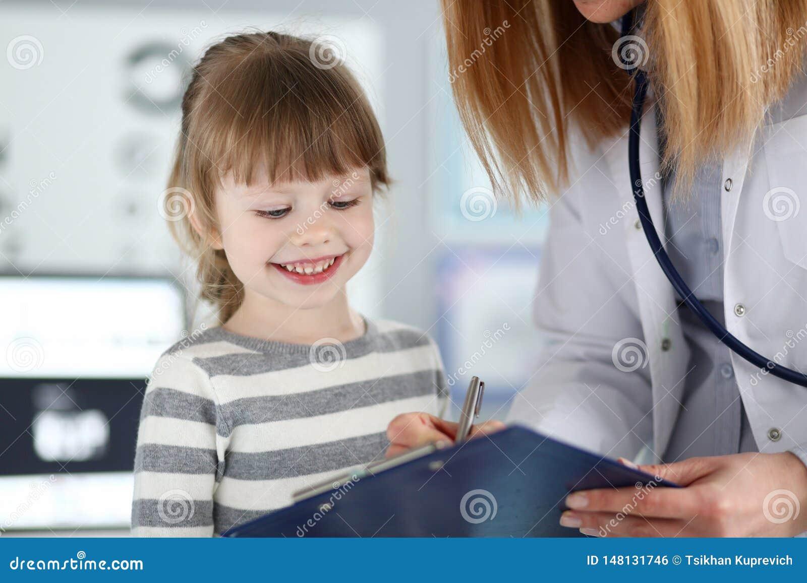 Kobieta doktorski s?uchaj?cy ?liczny ma?y pacjent i pisa? rejestracyjnej informacji na schowka ochraniaczu