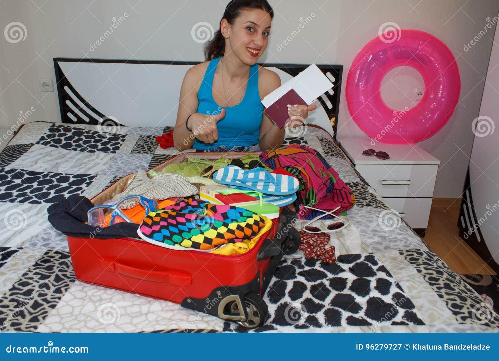 Kobieta Dostaje Przygotowywający Dla Podróżować młoda piękna kobieta, czerwona walizka, obsiadanie, czekanie, wakacje podróżuje a