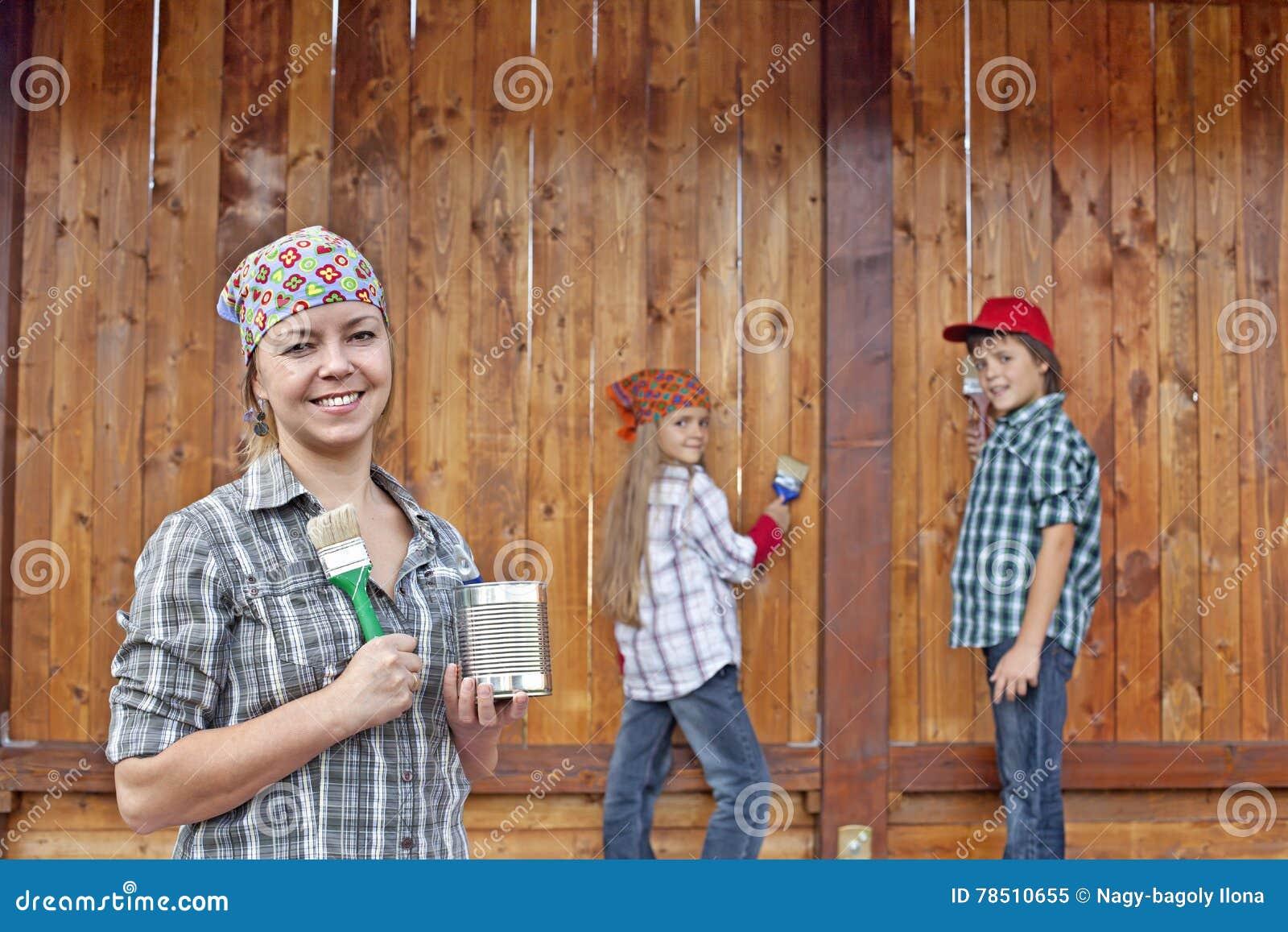 Kobieta i dzieciaki maluje drewnianą jatę