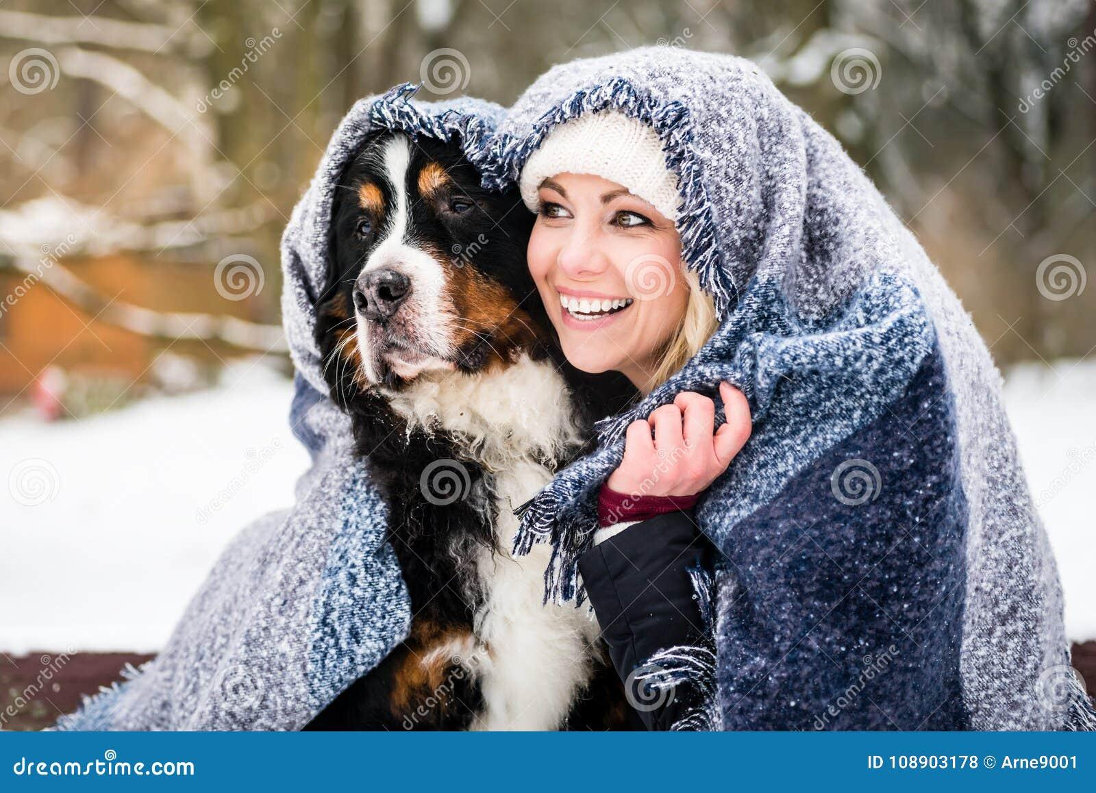 Kobieta i jej psi dostawać ciepły na zimnym zima dniu pod blanke