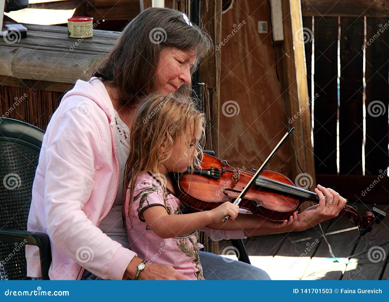 Kobieta i mała dziewczynka bawić się skrzypce na Akustycznym festiwalu muzykim w Floryda