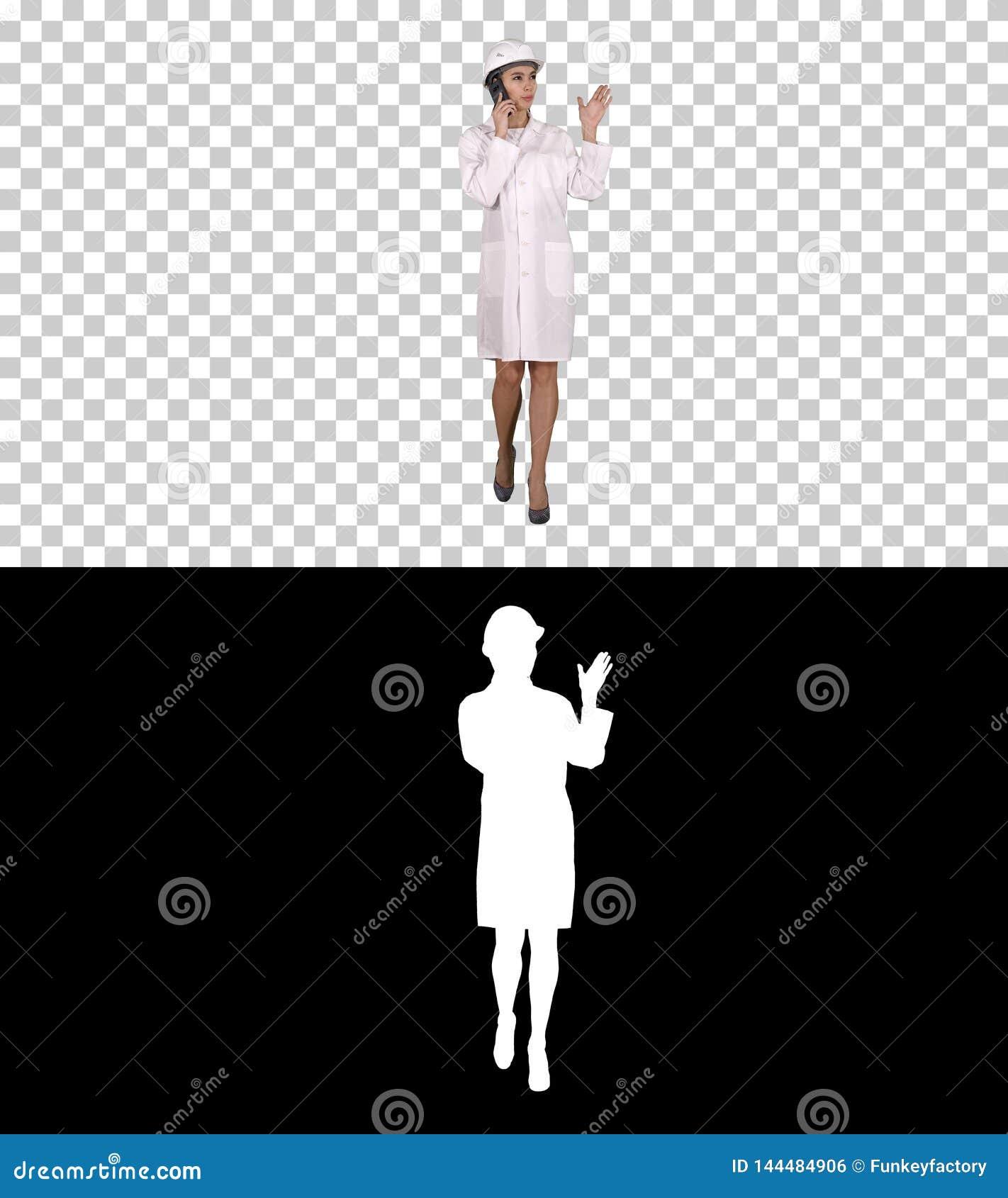 Kobieta inżynier opowiada na telefonie podczas gdy chodzący, Alfa kanał